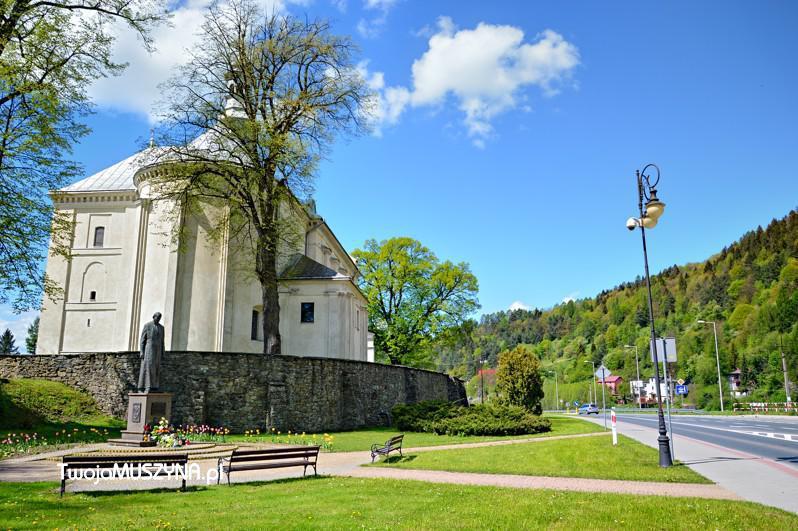 Kościół od strony drogi z pomnikiem ku czci św. Jana Pawła II